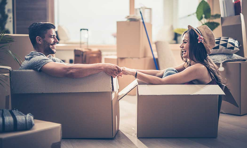 Couple sitting in moving boxes in new home